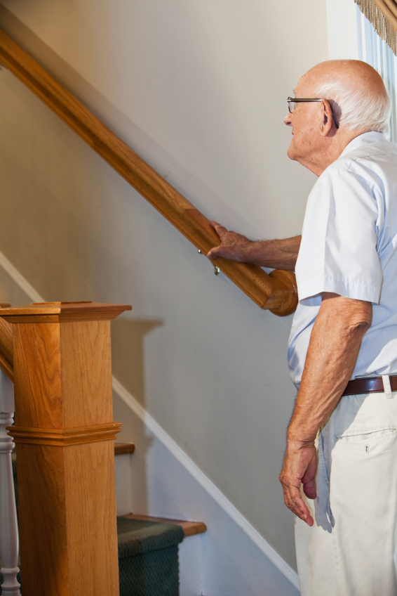 Elderly man at bottom of staircase looking up